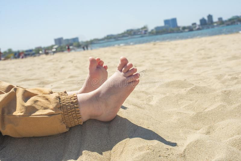 Bare children`s feet on the beach. close-up stock image