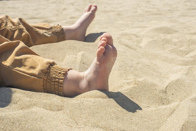 Bare children`s feet on the beach. close-up royalty free stock images