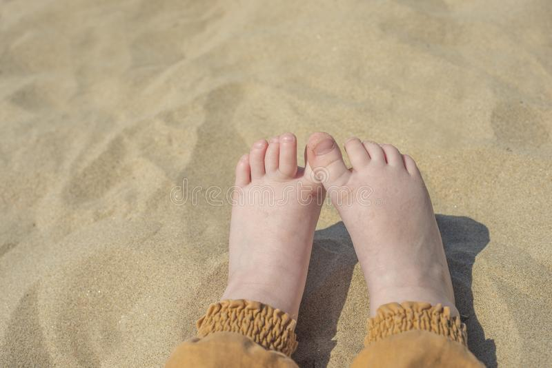 Bare children`s feet on the beach. close-up royalty free stock photos