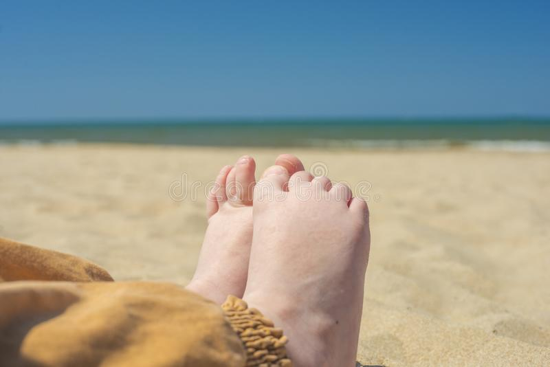 Bare children`s feet on the beach. close-up stock photo