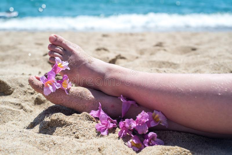 Bare feet on the beach, yellow sand, an exotic flower on the toes of the feet, hot sun, blue sea. Summer and holiday. S royalty free stock photos