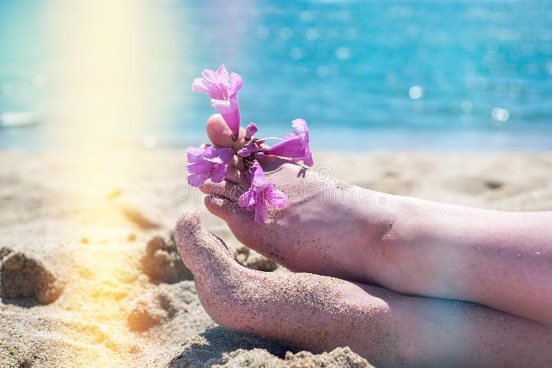 Bare feet on the beach, yellow sand, an exotic flower on the toes of the feet, hot sun, blue sea. Summer and holiday royalty free stock photo