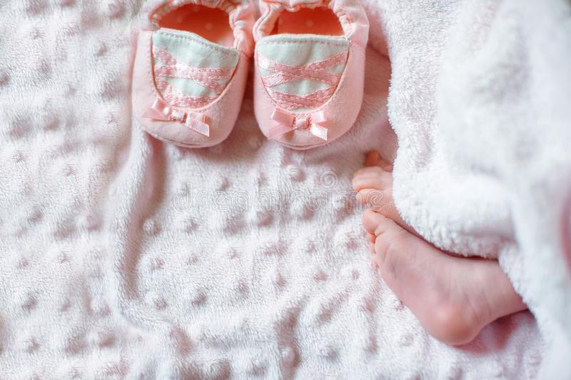 Bare feet of a cute newborn baby in warm white blanket. Childhood. Small bare feet of a little baby girl. Sleeping royalty free stock photos