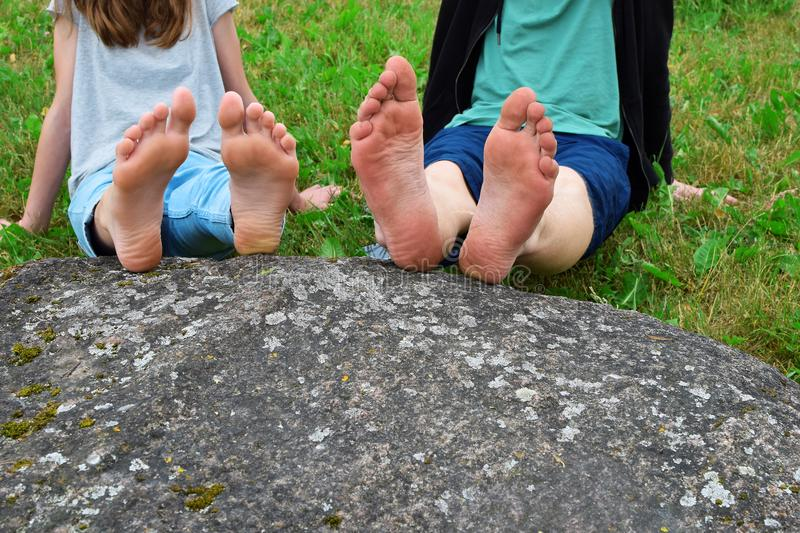 Bare feet of girl and boy on rock stock images