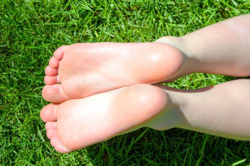 Bare feet in green grass stock photo
