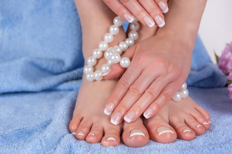 Bare feet and hands with french manicure and pedicure in spa salon on blue blue towel with decorative flower and pearls royalty free stock photo