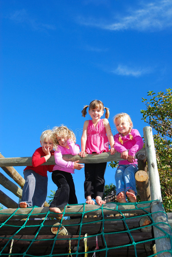 Bare feet kids. A family group of four caucasian children with happy smiling facial expression standing on top of a jungle gym on the playground outdoors