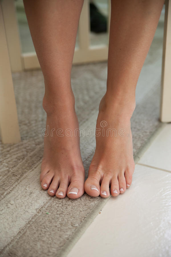 Bare feet and legs of woman. Of teenager on carpet and floor tiles stock photos