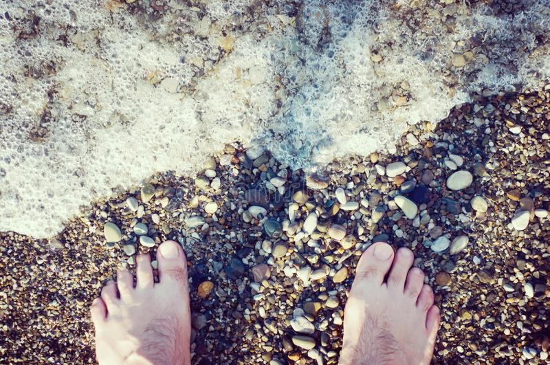 Man on pebble beach royalty free stock photography