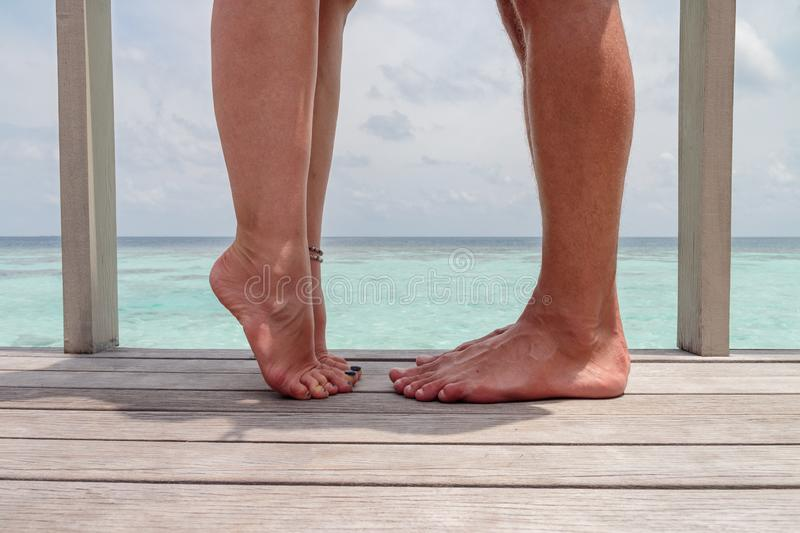 Closeup photo of woman and man legs, girl with raised leg. Couple kissing,  over sea background, he vs she royalty free stock images