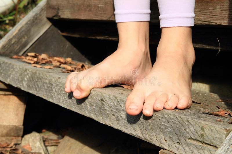 Bare feet on stair. Bare feet of a little girl - child standing on wooden stair stock image