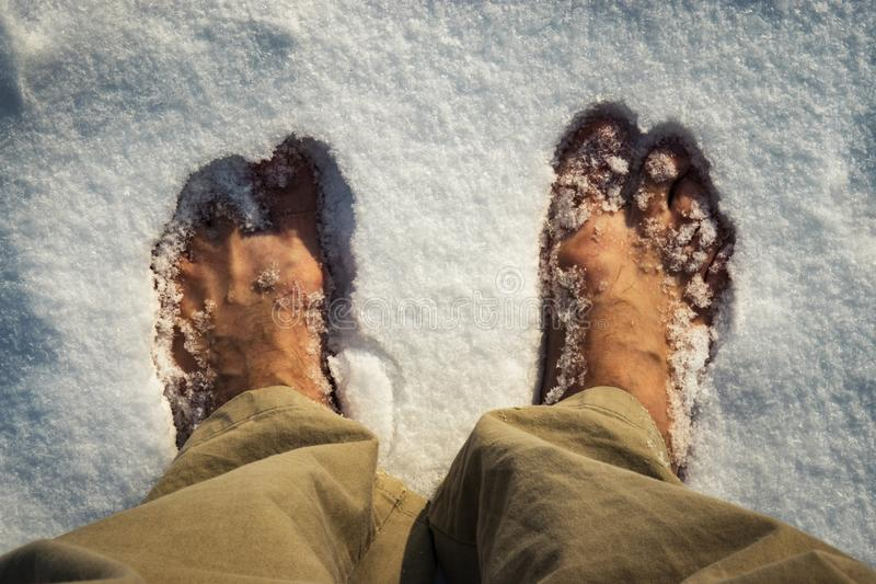 Bare feet in white snow royalty free stock photography