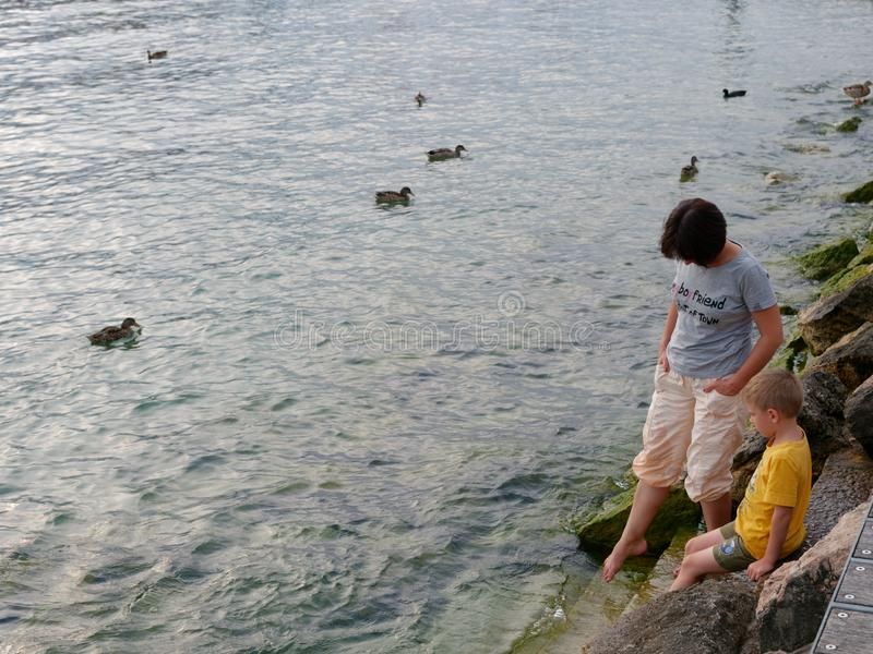Bare feet of a woman and a child by the water royalty free stock photography