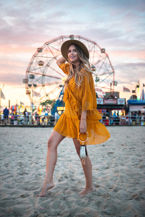 Bare feet woman walking on the beach sand in hand at sunset time near amusement park rides stock photo