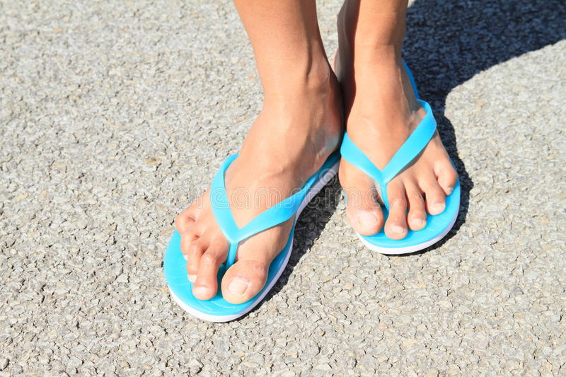Bare in flip-flops. Bare feet in flip-flops of a young woman - girl standing on asphalt stock images