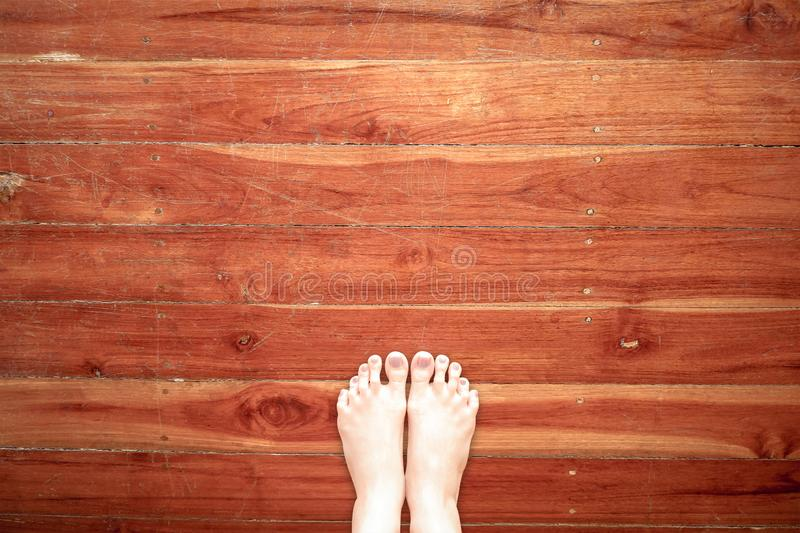 Bare Foot Standing on Wooden Floor Background, Top View. Selfie of Woman Bare Feet and Leg on Wood. Cropped Image of Beautiful royalty free stock photo