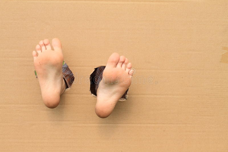 Bare soles of feet. Bare soles of little kid girl feet getting thru the paper stock photography
