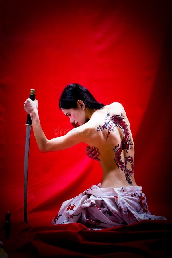 Bareback Geisha. A woman dressed like a Giesha with a dragon tattoo on her bare back and a Katana sword in her hand stock images