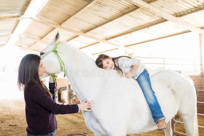 Mother And Daughter Showing Pure Friendship Towards Horse royalty free stock photo