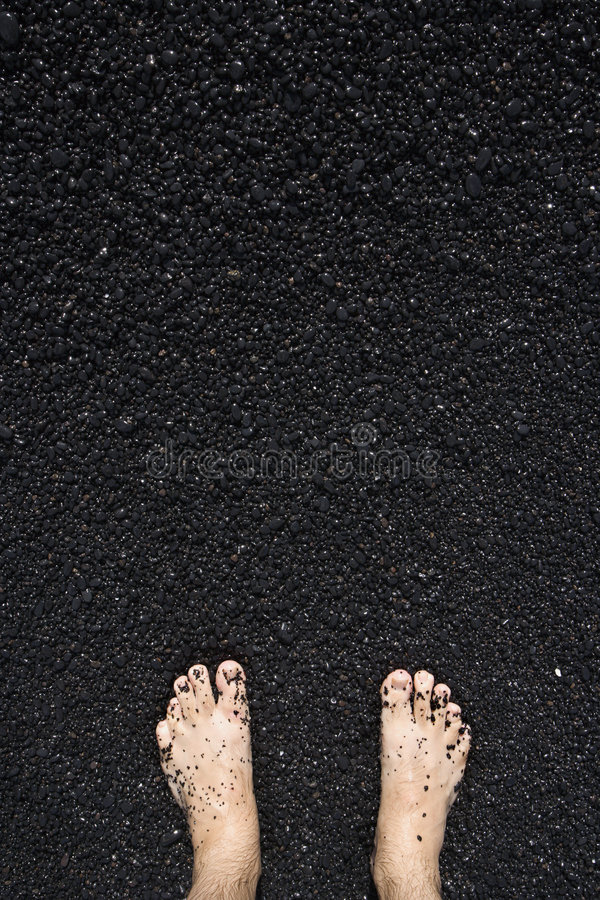 Barefeet in black sand royalty free stock photography