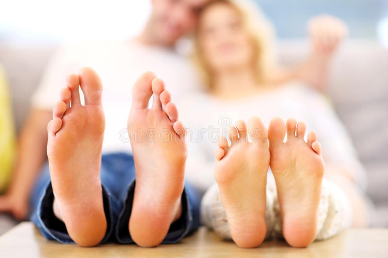 Barefeet of a happy couple lying on a sofa royalty free stock photo