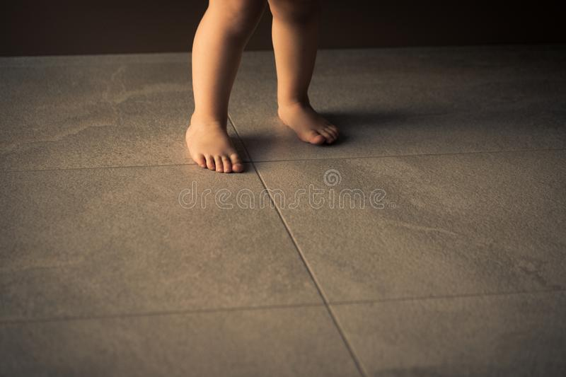 Barefoot baby are staying on heating tile floor.  stock photography