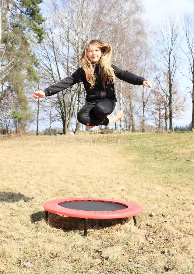 Barefoot Blond Girl Jumping On Trampoline Stock Photo -9462