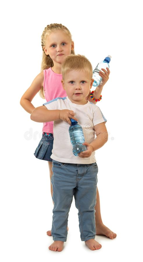 Barefoot boy and girl are standing side by side. Barefoot boy and girl are standing e by e, holding water bottle isolated on white background royalty free stock photos