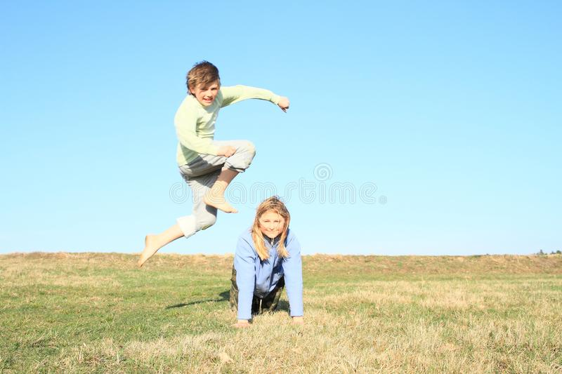 Barefoot boy jumping over girl. Hairy barefoot kid - young barefoot boy with jumping over young smiling blond girl dressed in blue jacket kneeling on grass of royalty free stock photography