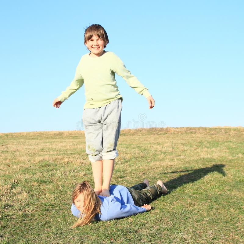 Barefoot boy standing on girl. Laughing kids. Young barefoot boy standing on back of young smiling hairy girl lying on grass of meadow with clear blue sky behind stock photos