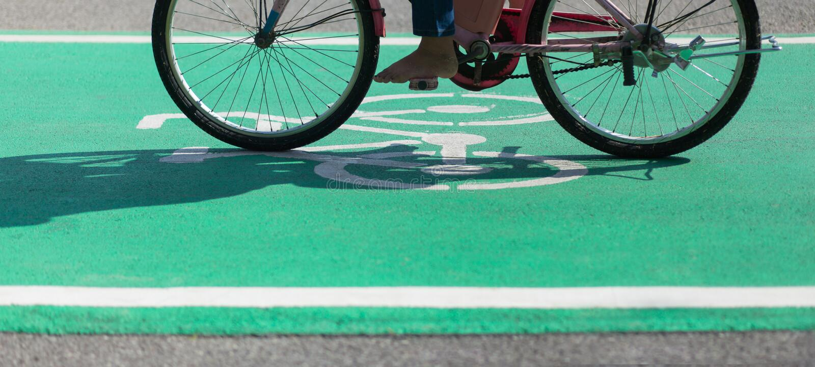 Barefoot Cycling on Bike Path Green Lane with the Bikeway Symbol stock images