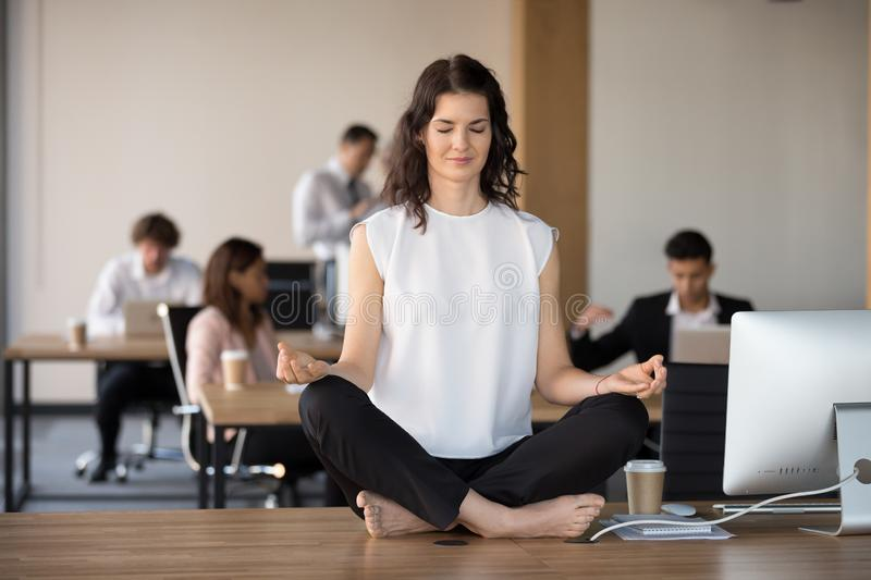 Barefoot employee meditating sitting in lotus position on office. While diverse colleagues working, attractive young employee in coworking area sitting on office stock image