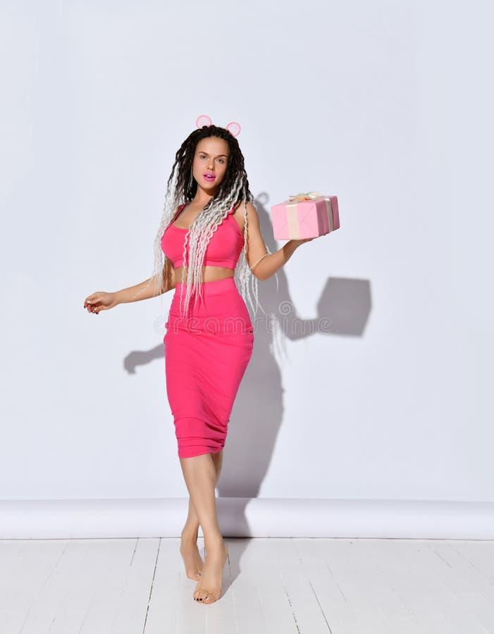 Barefoot femmina con piccioni africani Vestiti in gonna e in top rosa, con scatola regalo Camminando contro lo sfondo di una foto fotografia stock libera da diritti