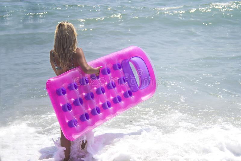 Barefoot girl in blue bikini at the sea. Slim tall girl in swimwear walking in the sea with pink inflatable pool raft stock photography
