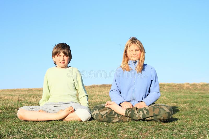 Kids exercising yoga. Barefoot girl and boy - young kids training yoga on green meadow. Easy pose - sukhasana. Childhood concept stock photography