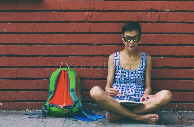 Barefoot girl draws sitting near a brick wall stock image
