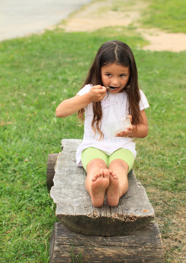 Barefoot girl eating. Little barefooted girl with long brown hair in white t-shirt and green shorts sitting on wooden bench and eating with spoon from glass bowl royalty free stock photos