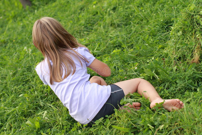 Barefoot girl on grass stock images
