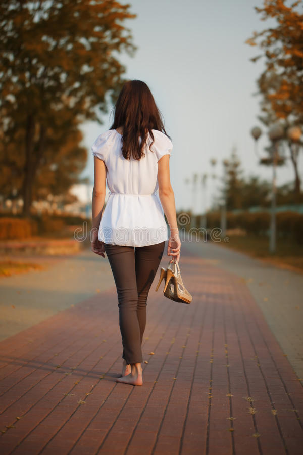 The barefoot girl with shoes in hand. Rear view stock photography