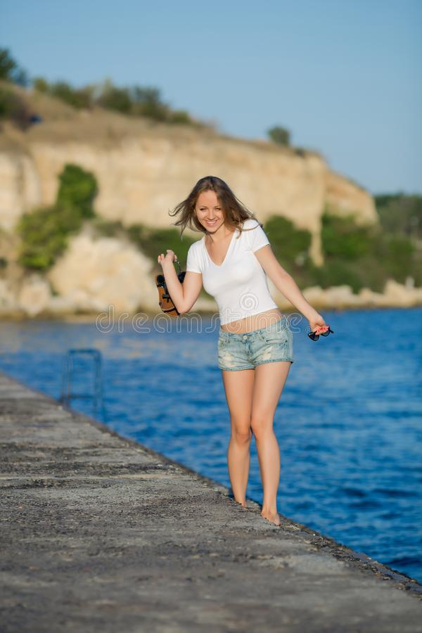 Barefoot girl in shorts walking on wet concrete quay royalty free stock photography