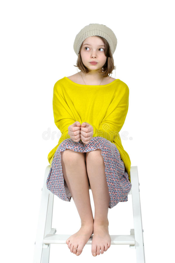 Barefoot girl sitting on a stepladder with a mysterious look. stock images