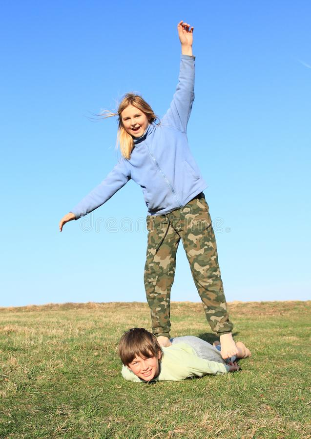Barefoot girl standing on boy. Laughing kids. Young barefoot girl with blond hair dressed in khaki pants and blue jacket standing on back of young smiling boy stock images
