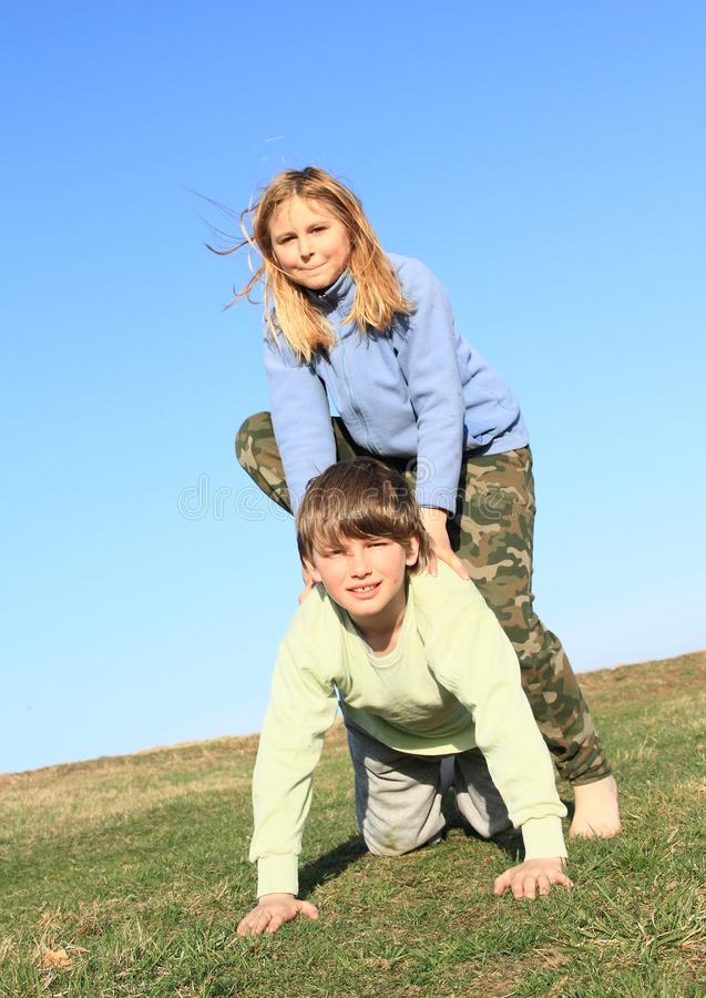 Barefoot girl stepping on boy. Hairy barefoot kid - young smiling girl with blond hair dressed in khaki pants and blue jacket standing on young smiling boy royalty free stock photos