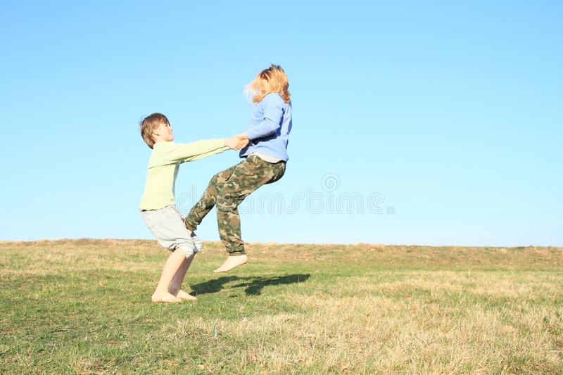 Barefoot girl stepping on boy. Hairy barefoot kid - young barefoot girl with blond hair dressed in khaki pants and blue jacket stepping on knees of young smiling royalty free stock photos