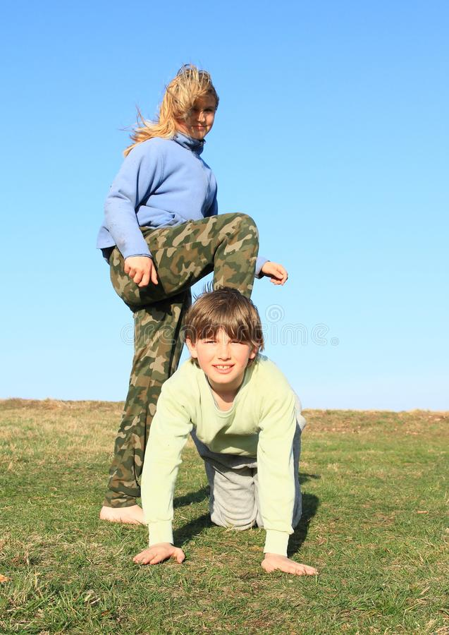Barefoot girl stepping on boy. Hairy barefoot kid - young smiling girl with blond hair dressed in khaki pants and blue jacket standing on young smiling boy royalty free stock photography