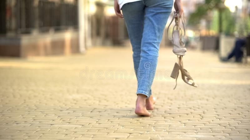 Barefoot girl walking down street holding in hands high-heeled sandals, freedom royalty free stock images