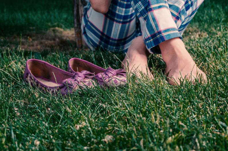 Barefoot harmony, girl sitting crosslegged on grass with her shes near. Shot with copyspace on foreground royalty free stock images