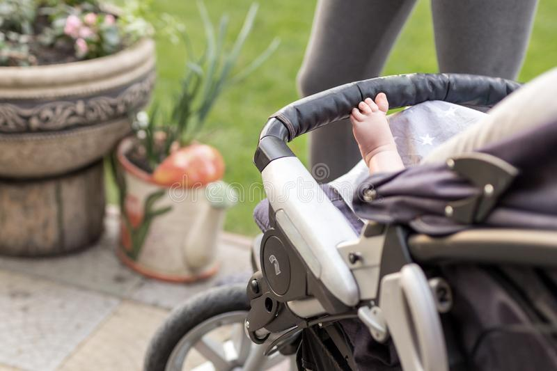 Barefoot kid leg in comfortable stroller.. Child sitting in baby carriage during walk outdoors.Sporty mother on background. Brigh stock photos