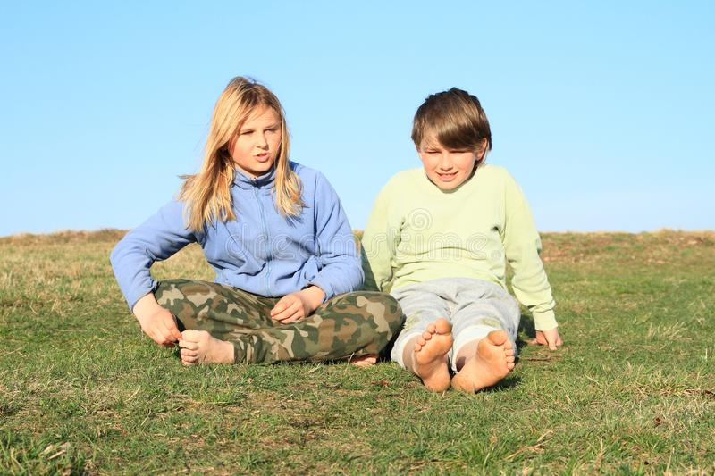 Friends sitting on meadow. Barefoot kids talking - young girl and boy sitting on grass of meadow with blue sky behind. Friendship concept stock photo