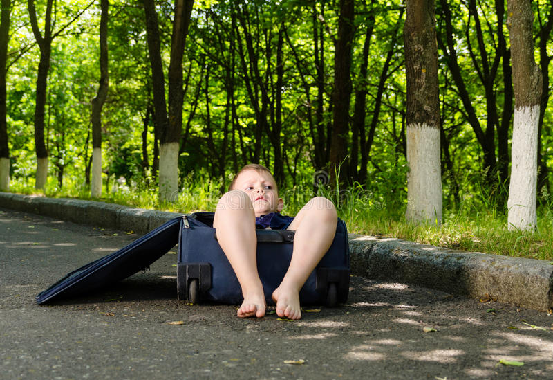 Barefoot little boy inside a suitcase royalty free stock photos